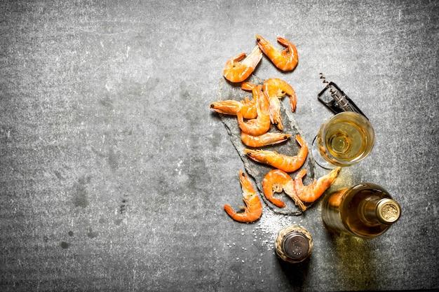 Botella de vino blanco con camarones en mesa de piedra.