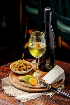 Una botella de vino blanco con una copa de frutos secos y queso sobre madera.