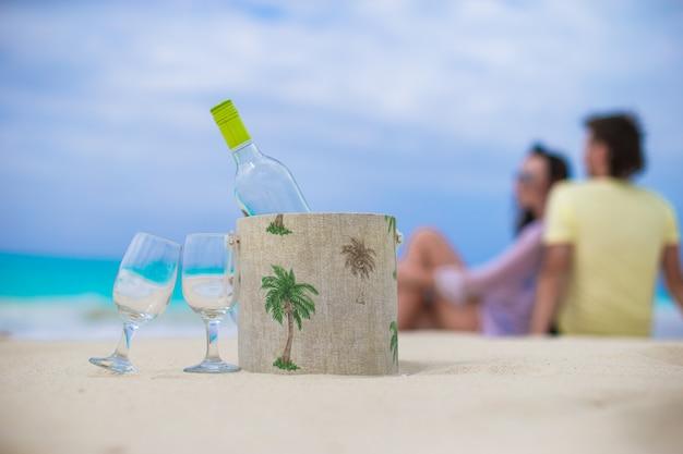 Botella de vino blanco y dos copas en la exótica playa de arena.