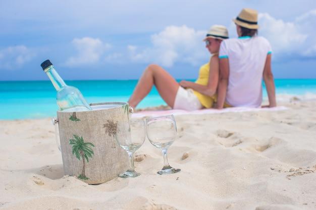 Botella de vino blanco y dos copas fondo feliz pareja en la playa de arena