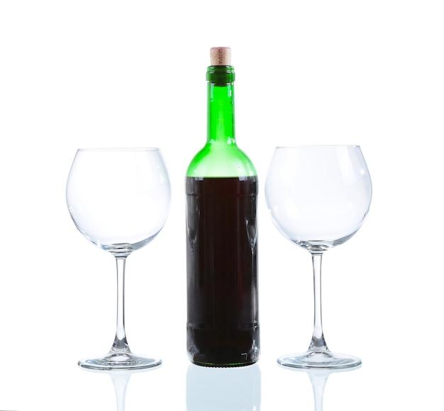 Botella de vino blanco y dos vasos vacíos. aislado sobre fondo blanco