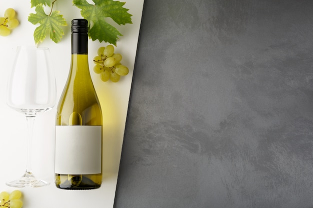 Botella de vino blanco con etiqueta. copa de vino y uva. maqueta de botella de vino.