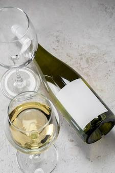 Botella de vino blanco con etiqueta vacía y vasos, logo de maqueta sobre fondo blanco.