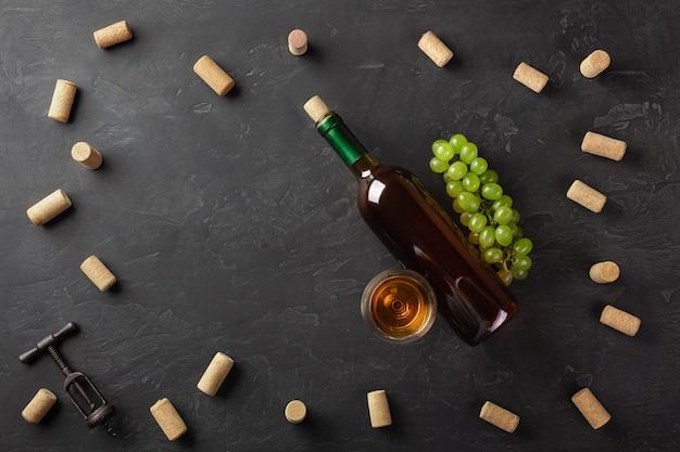 Botella de vino blanco, racimo de uvas y copa de vino con corchos y sacacorchos sobre fondo negro. vista superior con espacio de copia.