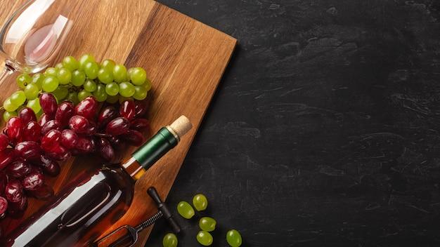 Botella de vino blanco, racimo de uvas y copa de vino sobre tabla de madera y fondo negro. vista superior con espacio de copia.