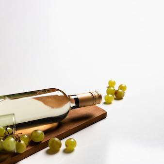 Botella de vino blanco en tabla de cortar
