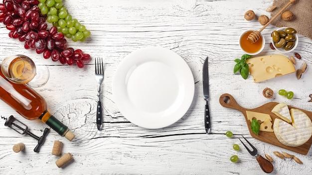 Botella de vino blanco, uva, miel, queso, copa de vino, plato, cuchillo y tenedor sobre tabla de madera blanca. vista superior con espacio de copia.