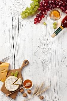 Botella de vino blanco, uva, miel, queso y copa de vino sobre fondo de tablero de madera blanca