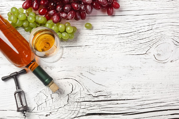 Botella de vino blanco, uva, miel, queso y copa de vino sobre tabla de madera blanca. vista superior con espacio de copia.