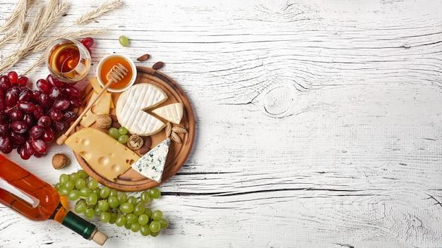 Botella de vino blanco, uva, miel, queso y copa de vino sobre tabla de madera blanca