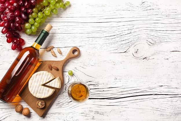 Botella de vino blanco, uva, queso y copa de vino sobre tabla de madera blanca. vista superior con espacio de copia.