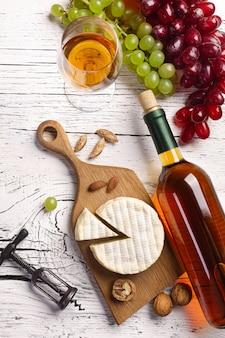 Botella de vino blanco, uva, queso y copa de vino sobre tabla de madera blanca
