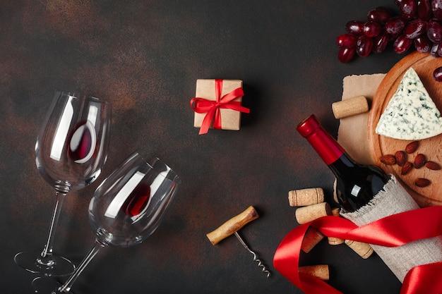 Botella de vino, caja de regalo, queso azul apestoso, uvas rojas, almendras, sacacorchos y corchos, sobre fondo oxidado.