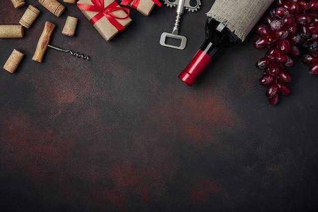 Botella de vino, caja de regalo, uvas rojas, sacacorchos y corchos.