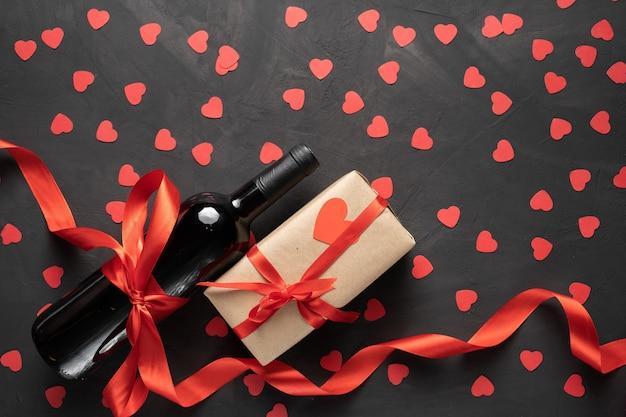Una botella de vino cerca de la caja empaquetada. día de san valentín. sobre un fondo de hormigón con corazones de papel. espacio libre para tu texto