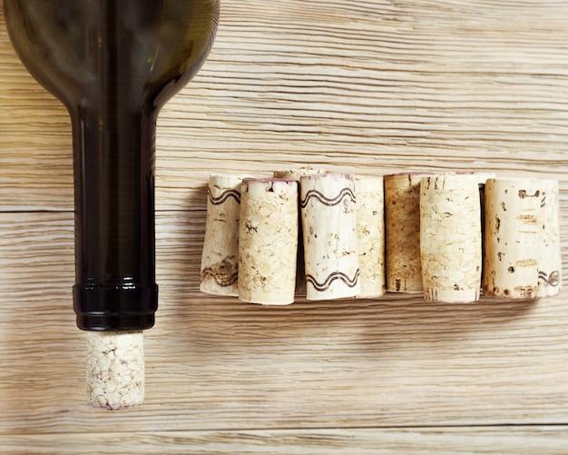 Una botella de vino cerrada con un tapón en la madera. corchos y cuello de botella de cerca. enfoque selectivo. vista superior.