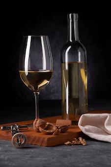 Botella de vino y copa con abridor.