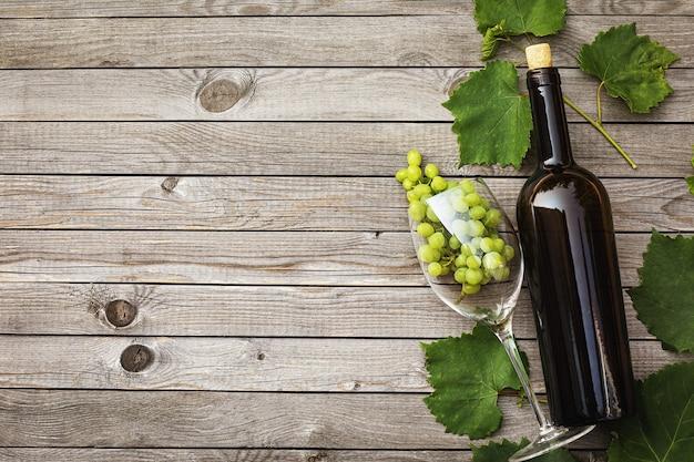 Botella de vino con una copa y un racimo de uvas en una mesa de madera con espacio de copia