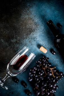 Botella de vino con copa y uvas.