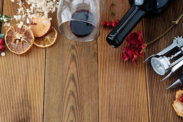 Botella de vino con copa de vino sacacorchos rústico tablero de madera, copyspace. endecha plana.