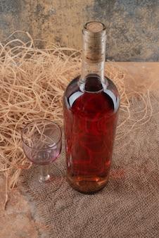 Botella de vino con copa de vino sobre arpillera.