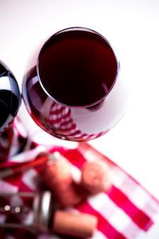 Botella de vino con copa de vino sobre fondo blanco de madera