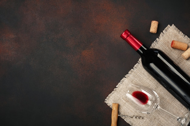 Botella de vino, copas, sacacorchos y corchos, en la vista superior de fondo oxidado