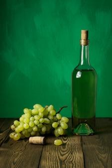 Botella de vino de cristal con corchos en el fondo de la mesa de madera