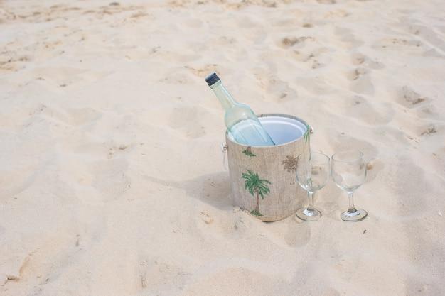 Botella de vino y dos copas en la playa de arena