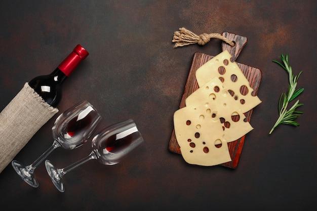 Botella de vino, dos copas y queso maasdam en rodajas sobre una tabla de cortar sobre fondo oxidado
