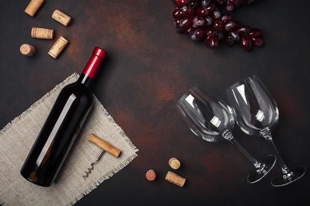 Botella de vino, dos copas, sacacorchos y corchos, en la vista superior de fondo oxidado, espacio de copia