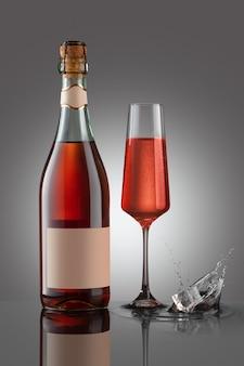 Botella de vino espumoso lambrusco rosato con copa de vino. salpicaduras de cubitos de hielo.