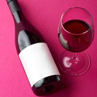 Botella de vino con una etiqueta en blanco recostada sobre su costado y copas de vino llenas