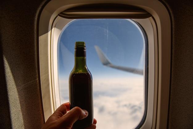 Botella de vino frente al ojo de buey. alcohol a bordo de un avión.