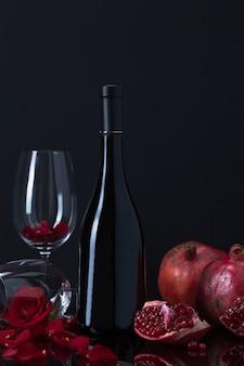 Botella de vino con granadas, copas y pétalos de rosa.