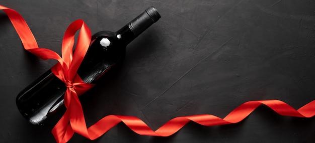 Botella de vino con lazo de cinta de raso rojo. día de san valentín. sobre un fondo de hormigón. espacio libre para su texto.