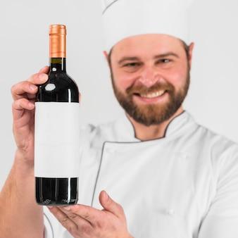 Botella de vino en manos del chef cocinero.