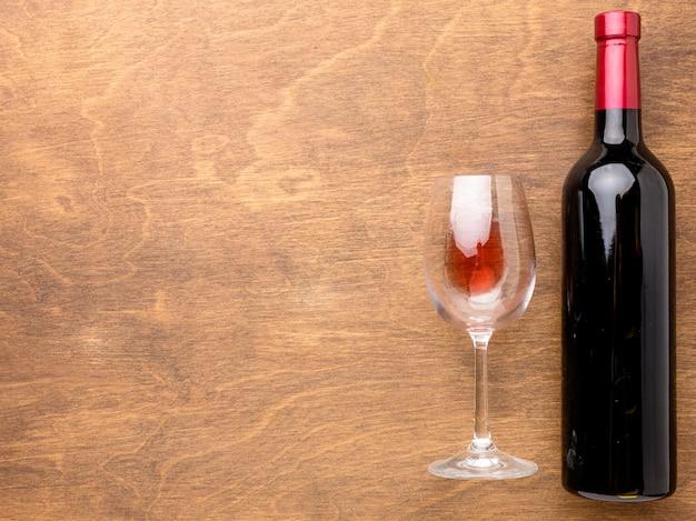 Botella de vino plana y vaso con espacio de copia