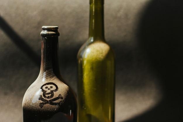 Botella de vino polvoriento con calavera y huesos pintados