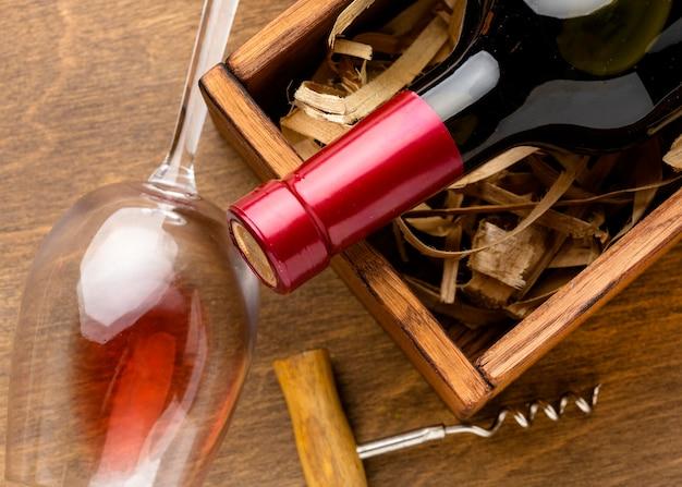 Botella de vino de primer plano y vaso con sacacorchos