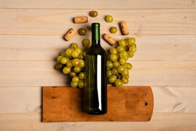 Botella de vino puesta en tabla de cortar cerca de uvas
