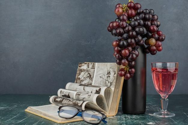 Botella de vino y racimo de uvas negras sobre mesa de mármol con libro y vasos.