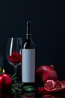 Botella de vino con rosa en copa, vela, granada y planta.