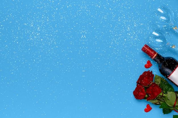 Botella de vino, rosas y copas de vino con copos de nieve sobre fondo azul vista superior con lugar para insertar texto. concepto de día de san valentín