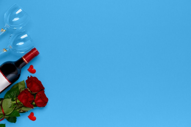 Botella de vino con rosas y copas de vino en la vista superior de fondo azul. día de san valentín