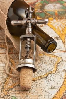 Botella de vino y un sacacorchos en el fondo de mapas antiguos