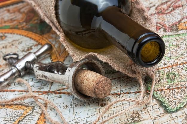 Botella de vino y un sacacorchos en el fondo de viejos mapas
