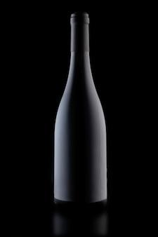 Una botella de vino sobre un fondo negro, foto vertical de primer plano.