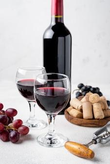 Botella de vino tinto de alto ángulo y copas con vino