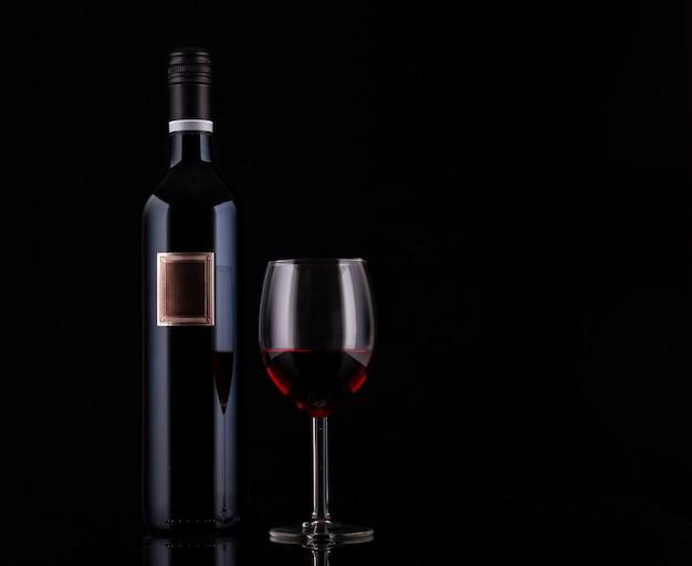 Botella de vino tinto cerrado con etiqueta vacía y copa de vino sobre fondo negro con reflejos
